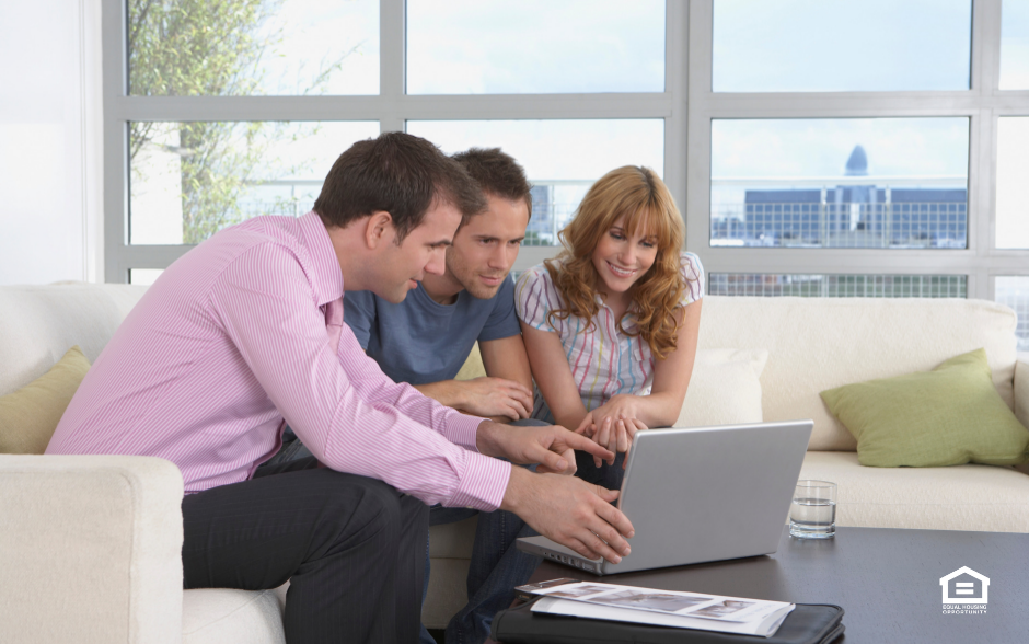 Real estate agent with couple looking at computer
