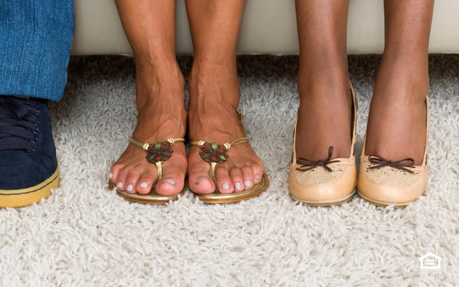 People's feet on white carpet.