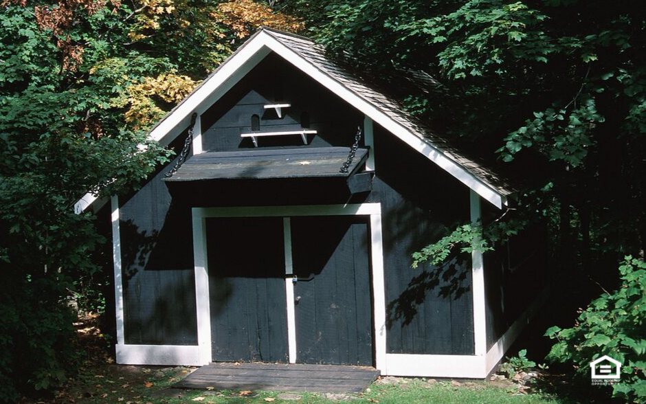 Gray storage shed surrounded by trees