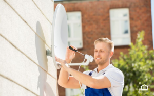 Man installing small satellite dish on side of house