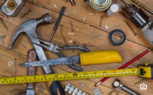 Home maintenance tools lying on a wood floor