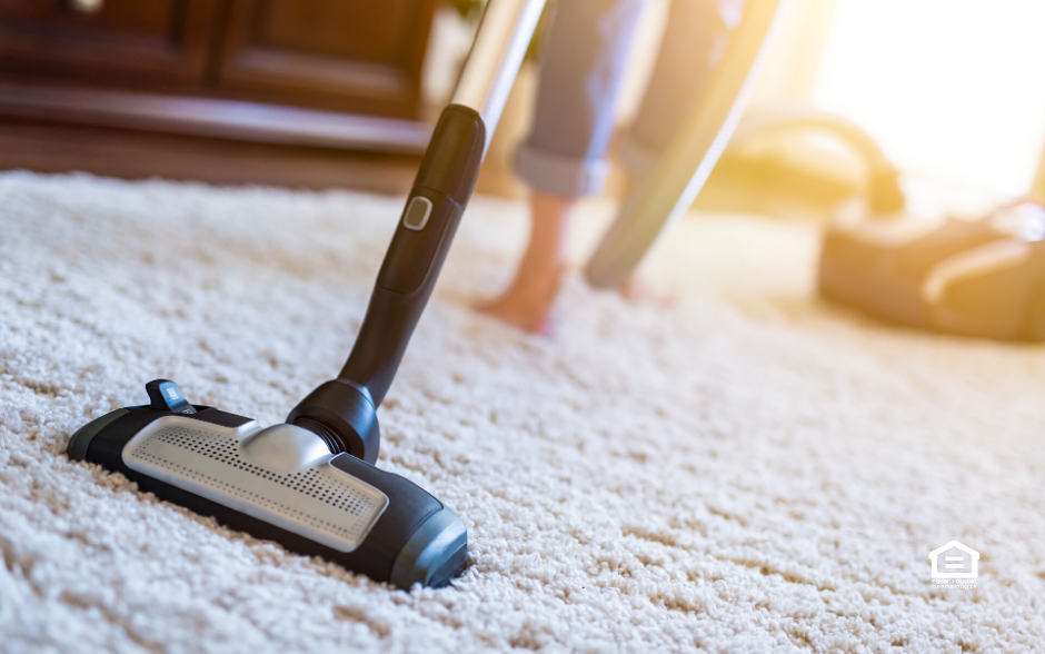 Woman with vacuum cleaning carpet in rental property