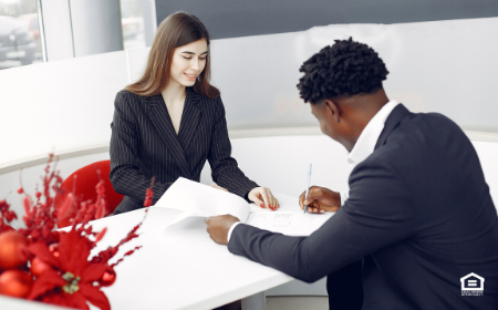 Man filling out tenant application at desk with woman on other side.