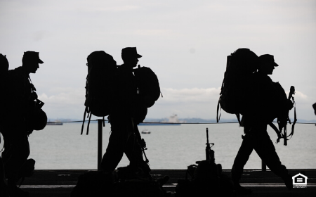 Silhouette of military personnel marching.
