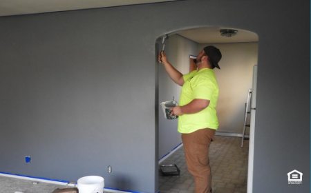Man painting a room entry way.
