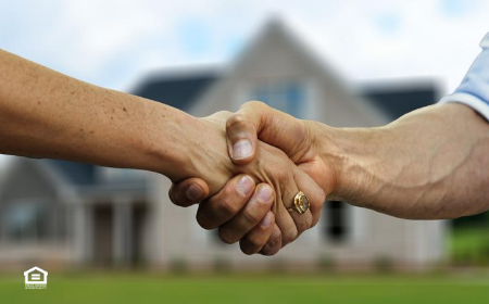 Landlord and tenant shaking hands in front of house
