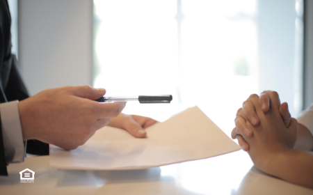 Close up of two people's hands on a table reviewing landlord insurance papers.