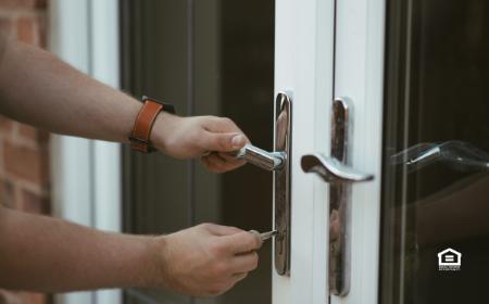 Hands locking door house to prevent squatters.