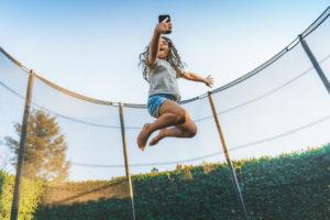 Little Girl Jumping on Trampoline in Backyard