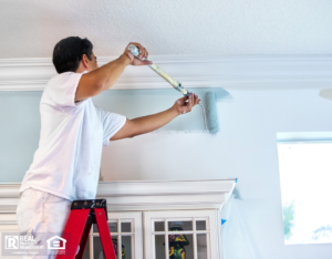 Leon Valley Property Owner on Ladder Painting Interior Walls with Roller
