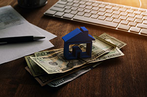 Blue Model House Stacked on Pile of Money
