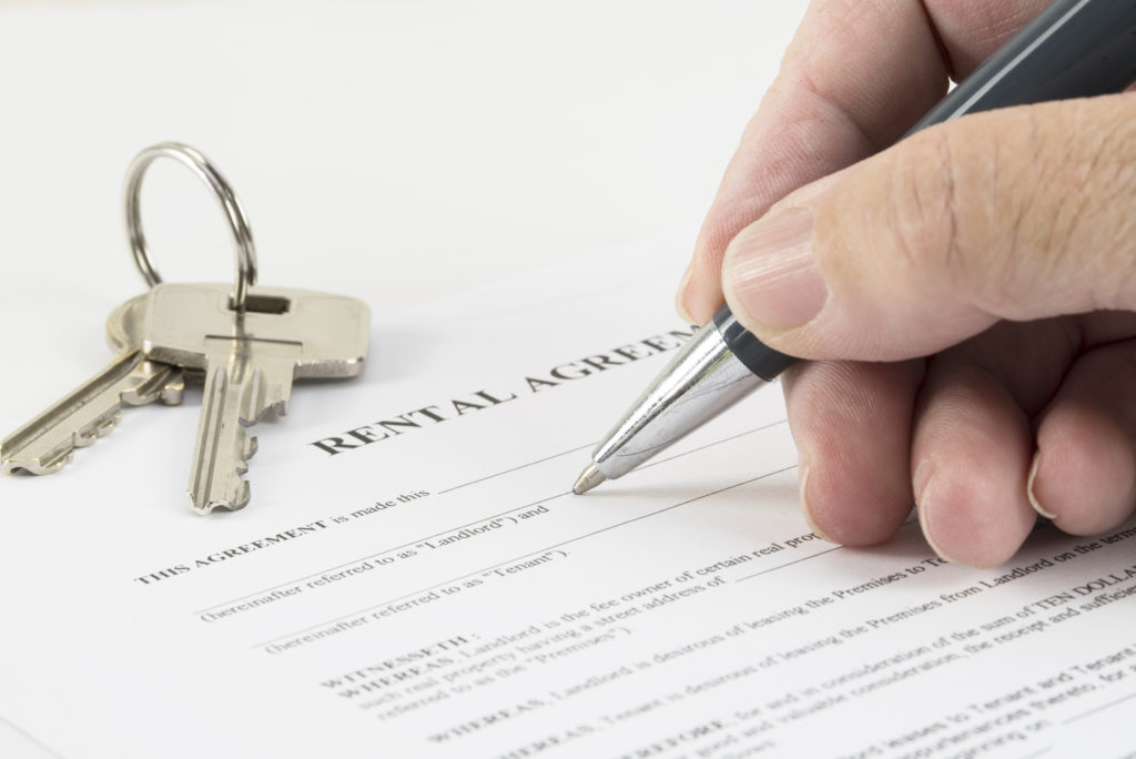 hand is writing with a pen on a rental agreement document, house keys in the background