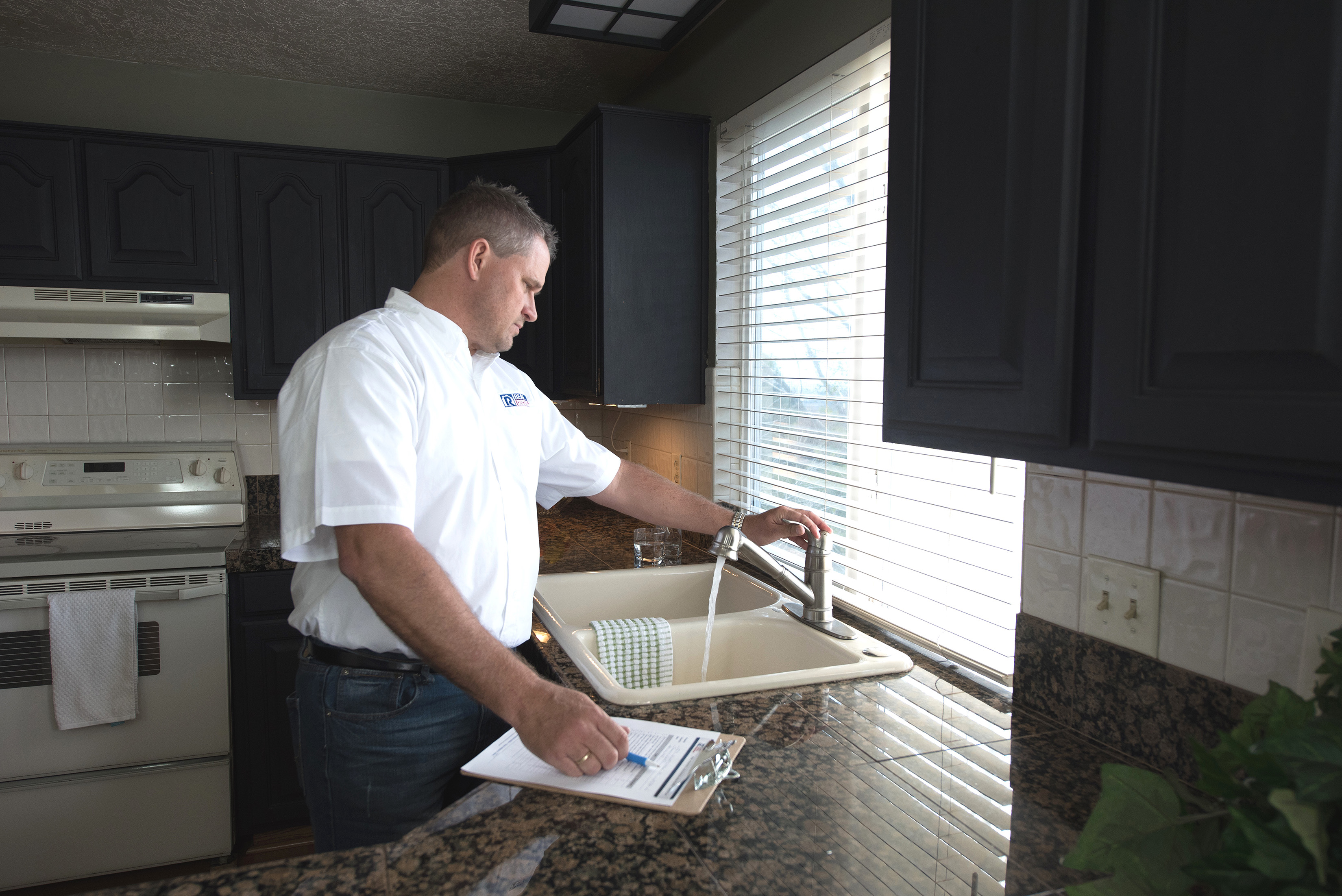 Real Property Management staff inspecting the sink