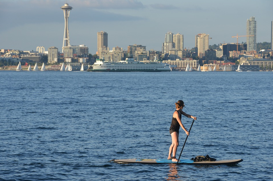 Woman Paddleboarding along the Puget Sound Coastline