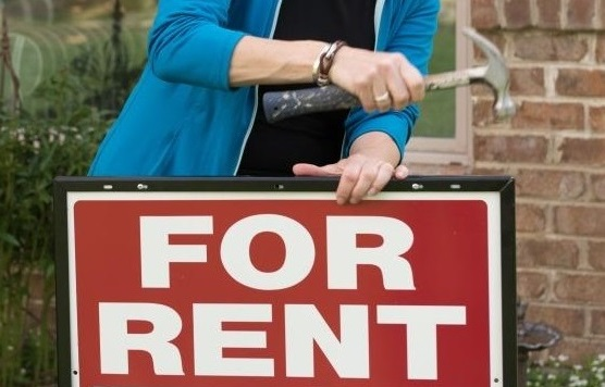 "Someone putting a ""For Rent"" sign in front of a rental house in Baton Rouge"