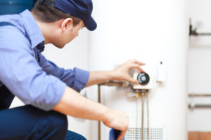 Man Fixing a Water Heater in Central Rental Property