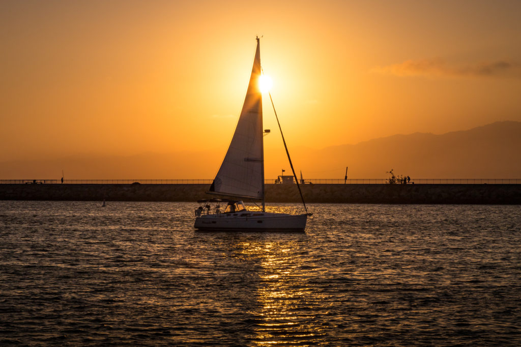 Sailboat sailing into Marina del Rey, California at sunset with clouds in the sky and the Santa Monica Mountains in the background