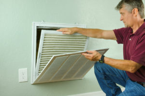 Mystic Homeowner Replacing Air Filter on Their Air Conditioner