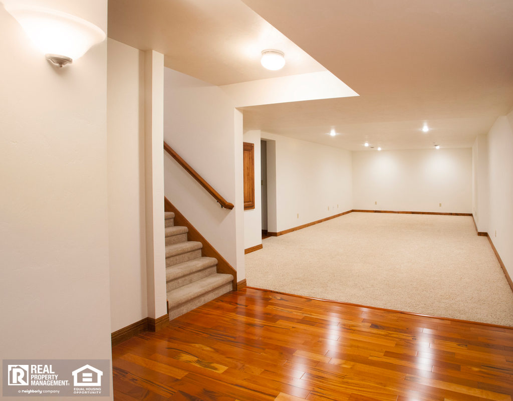 View of the Newly Finished and Unfurnished Basement with Hardwood Flooring