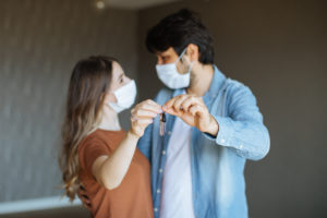 Couple with Face Masks Holding Keys to Their Norwalk Apartment