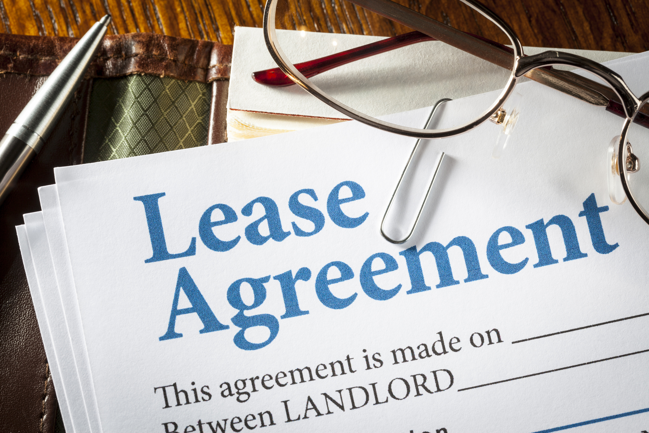 Lease agreement with pen and glasses on desk