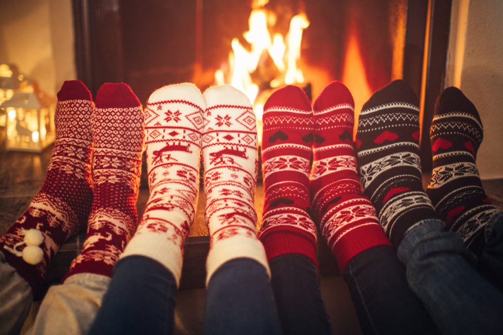 four friends wearing colourful wool socks warming their feet by the fireplace