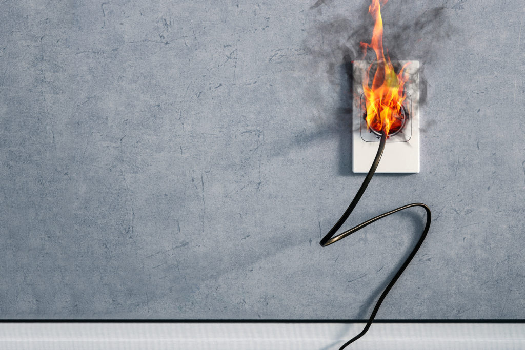 fire and smoke on electric wire plug in indoor, electric short circuit causing fire on plug socket