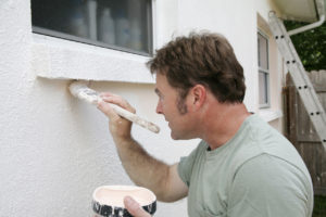 Man Painting the Exterior of a Grand Rapids Rental Property