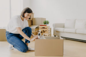 Happy Tenant with her Dog Playing in Moving Boxes