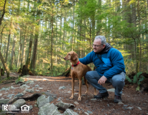 Mature Hiking Man Holding Vizsla Dog in Sunlit Forest