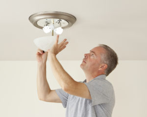 Garner Property Manager Placing Energy Efficient Lightbulbs in a Fixture