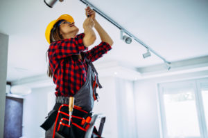 Woman in Hardhat Working on Lighting Fixture in Rental Property