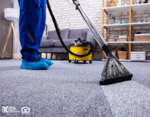 Professional carpet cleaner working in living room of rental property