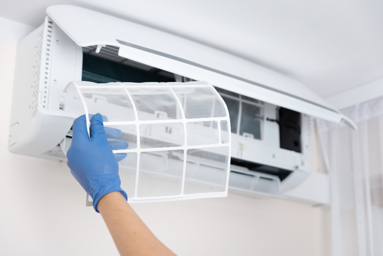 Property manager cleaning air conditioner filter