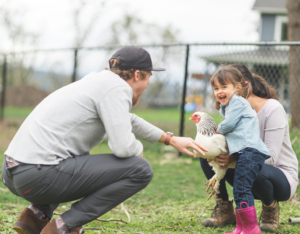 Happy Family Playing with a Chicken in the Yard of their Filer Rental Home