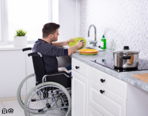 Woodward Tenant Cleaning Dishes in the Kitchen from His Wheelchair