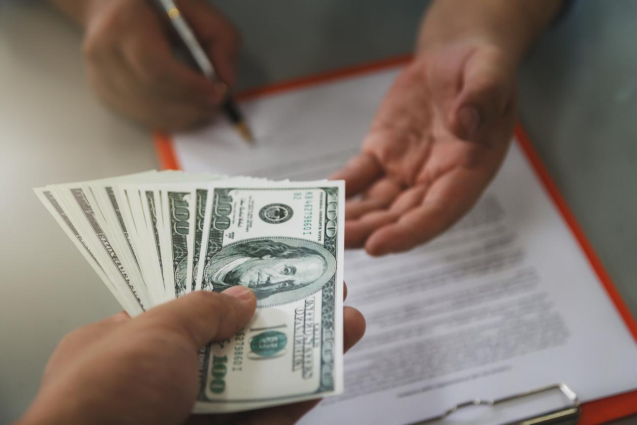 man paying rent in cash