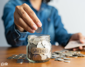 Woman Dropping Change into a Jar Labeled Savings