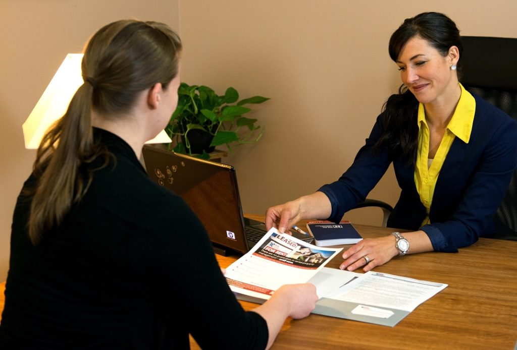Two women in an office discussing leasing material.