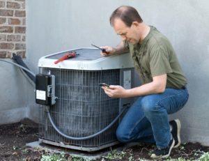Handyman Making Repairs to an Outdoor Air Conditioning Unit