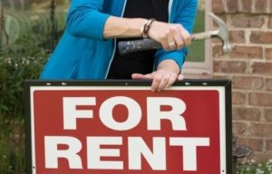 """Someone placing a """"For Rent"""" sign in the front yard of a rental house"""