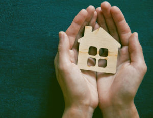 Hands holding house - property management