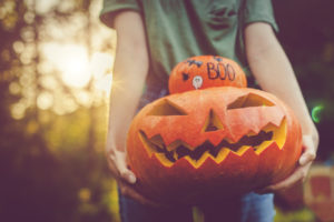 Fortuna Resident Holding a Stack of a Decorated Pumpkin and a Jack-o-Lantern