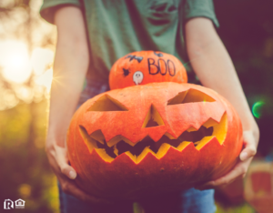 Davidson Resident Holding a Stack of a Decorated Pumpkin and a Jack-o-Lantern