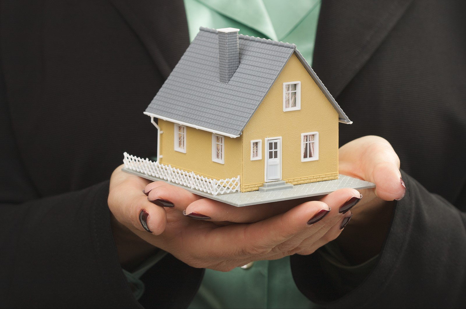 A Miniature Model of a Home Sitting in the Hands of a Property Manager