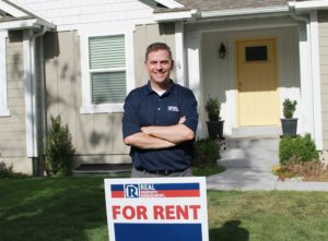 """Property Manager Standing Behind a Real Property Management """"For Rent"""" Sign"""