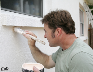 Man Painting the Exterior of a Galveston Rental Property