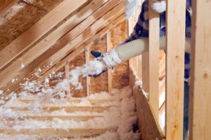Spraying Blow-In Fiberglass Insulation Between the Attic Trusses of Your Evansville Rental Home