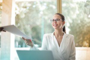 businesswoman handing over paperwork