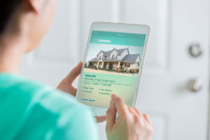 Woman on Tablet Looking at Temple Property Costs